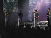 Colour photograph of Take That performing live in 2007.