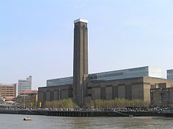 A large oblong brick building with square chimney stack in centre of front face. It stands on the far side of a river, with a curving white foot bridge on the left.