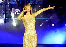 A young white woman singing on stage, wearing a sparkling bodysuit
