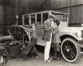 The Blacksmith - Buster Keaton hoists a Model T engine from a wrecked car as Virginia Fox flirts with an unidentified actor in a scene still for the 1922 comedy short The Blacksmith.