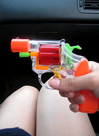 Toy Gun being held in car with legs in background.jpg