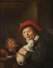 Två pojkar som leker med en katt
