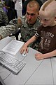 U.S. Army Staff Sgt. Craig Davis, left, a weapons operator with the 49th Missile Defense Battalion, guides a boy from the Fort Greely Child Development Center through a national defense simulation featuring an 120807-A-PV459-002.jpg