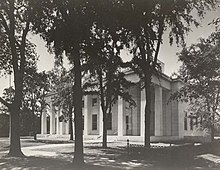 Building with columns behind trees.
