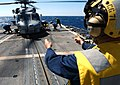 US Navy 030327-N-3235P-512 Boatswains' Mate 1st Class Jeremy M. Bangs signals to the pilot of an SH-60B, that personnel are on both sides of the aircraft, assigned to Helicopter Anti-submarine Light Squadron Four Four (HSL-44).jpg