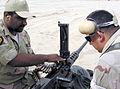 US Navy 030412-N-1050K-033 Pvt. Mubarek, a Kuwaiti Sailor assigned to a Force Protection Team loads a strand of ammunition into a M2 .50 caliber machine gun under the watchful eye of Gunner's Mate 2nd Class Miguel Martinez.jpg