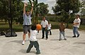 """US Navy 040219-M-7403H-007 U.S. Marine Sgt. Maj. Richard Dorsey, assigned to the """"Ugly Angels"""" of Marine Heavy Helicopter Squadron Three Six Two (HMH-362) plays basketball with children.jpg"""