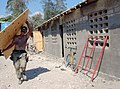 US Navy 050319-N-9594C-009 Builder 2nd Class Thomas Hurlburt, a Seabee assigned to Naval Mobile Construction Battalion One (NMCB-1), carries a sheet of plywood during construction of a three-room schoolhouse in Gonaives, Haiti.jpg