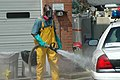US Navy 050919-N-9274T-002 Shawn Thomas of the New York Fire Department, uses a fire hose to clean tires of a police car with bleach and chlorine at a decontamination station.jpg