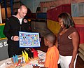 US Navy 060827-N-3609W-003 Personnel Specialist 1st Class Nathan Hazell explains signal flags to a young boy on Navy Day at the Louisiana Children's Museum.jpg