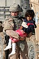 US Navy 061127-M-5585B-013 Spc. Taryn Emery attached to 2nd Battalion, 136th Infantry Regiment, holds a local girl in her arms during a combined humanitarian, medical, school and hygiene engagement operation in Qaryat Al Majarr.jpg