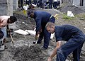 US Navy 070626-N-6410J-033 Chief Aviation Boatswain's Mate Earl Davis, center, shovels concrete mixture into a pile with the help of fellow Sailors from amphibious assault ship USS Peleliu (LHA 5) and local Filipinos.jpg