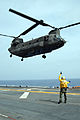 US Navy 090717-N-4846W-006 Aviation Boatswain's Mate (Handling) 2nd Class Della Smith, a landing signal enlisted (LSE) aboard the amphibious assault ship USS Makin Island (LHD 8), directs an Army CH-47 Chinook helicopter.jpg