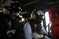 US Navy 100120-N-0727M-016 A Haitian woman carries her infant son aboard an SH-60S Sea Hawk helicopter from Helicopter Sea Combat Squadron (HSC) 26.jpg