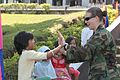 US Navy 100301-M-6309C-017 A Seabee gives a high-five to a girl at a ribbon-cutting ceremony for two school buildings at the Lanao Agricultural College at Barangay Lumbatan.jpg