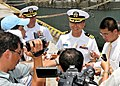 US Navy 100810-N-3215T-182 Cmdr. Jeffrey Kim speaks with Vietnamese reporters following the arrival of USS John S. McCain (DDG 56) to Da Nang, Vietnam.jpg