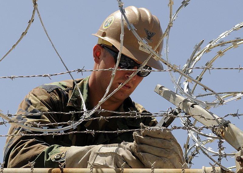 File:US Navy 100812-N-6357K-001 Builder 2nd Class Joshua McCart, assigned to Naval Mobile Construction Battalion (NMCB) 7, installs protective razor wire at the weapons armory at Camp Mitchell on Naval Station Rota, Spain.jpg