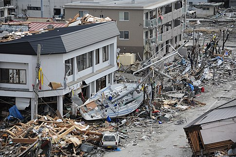 A fishing boat rests against a building in Ofunato. Image: U.S. Navy.