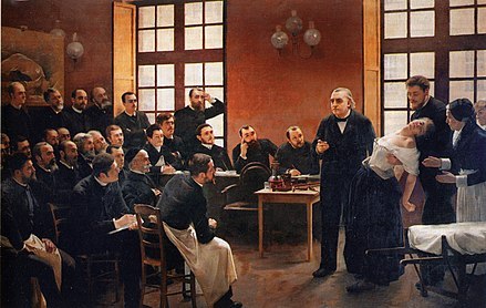 Andre Brouillet's 1887 A Clinical Lesson at the Salpetriere depicting a Charcot demonstration. Freud had a lithograph of this painting placed over the couch in his consulting rooms. Une lecon clinique a la Salpetriere.jpg