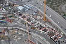 A construction site with several cranes and walls surrounding a long, rectangular hole in the ground.
