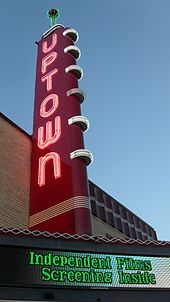 "A red sign with the word ""Uptown"" illuminated in white neon. The sky is darkening. There is an electronic marquee that reads ""Independent films screening inside""."