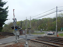 Train tracks going from lower right to mid-left cross, at grade, with metal plating around the tracks, a paved road going lower left to an intersection at a divided highway with a traffic light just above the tracks. Two railroad crossing signs with red-and-white-striped barriers in the up position are on either side of the tracks. A pine tree's branches protrude into the image from the left; across the divided highway are more woods, with trees beginning show leaf, slightly mited under an overcast sky