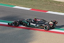 A black Formula One car drives between some gravel and some tarmac on a paved area painted in the colours of the Italian flag.