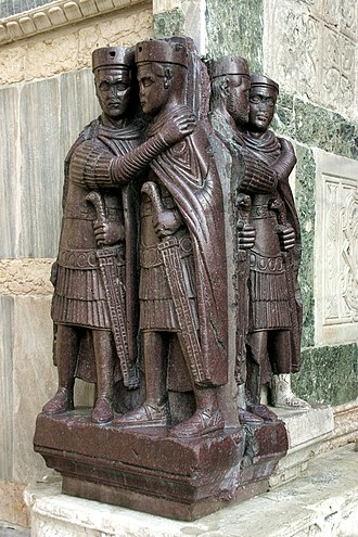 "Late Roman army - The Tetrarchs, a porphyry statue on Venice's Basilica di San Marco, shows the emperor Diocletian and his three imperial colleagues. To the left, Diocletian and Maximianus, the two Augusti (co-emperors); to the right, Galerius and Constantius Chlorus, the two Caesars (deputy emperors). Note the woollen ""Pannonian"" caps commonly worn (out of combat) by officers in the late army as a result of the pervasive influence of the Danubian officer class; and the sword grips with eagle-head pommels."