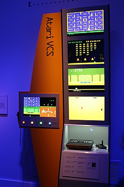 "Atari VCS on display at ""The Art of Video Games"" (2012) at the Smithsonian American Art Museum. Shown are Pac-Man (top), Space Invaders, Pitfall!, and Combat. Video Game Consoles Atari VCS.jpg"