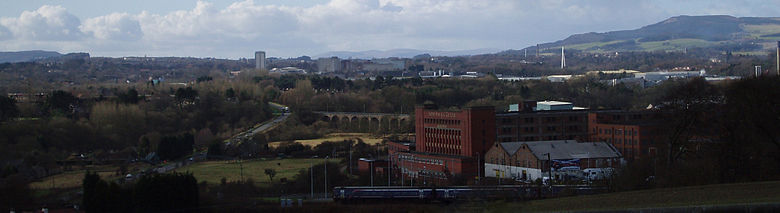 View of Glenrothes seen in its landscape setting from a nearby cemetery. A train is leaving nearby Markinch Station on the East Coast Mainline. Glenrothes town centre with the numerous taller residential and office buildings can be seen in the centre of the image. The River Leven Bridge provides a stark white vertical emphasis on the right side of the image. The Lomond Hills regional park and rolling countryside form the backdrop on the horizon