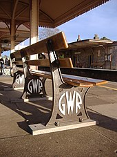 "A bench seen from low down and behind. Three brown-painted cast iron legs have ""G W R"" cast into them in a circular mofif and painted white, and support two pairs of widely spaced wooden planks that form the seat and back."
