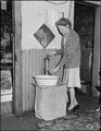 Young wife of a miner drawing water at the tap in her kitchen. This tap was installed by a former tenant, few houses... - NARA - 540942.tif