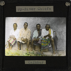 Group picture of four village chiefs visiting Okoyong. The four chiefs, all men, are sitting on a wooden box in front of a clay wall. To the right of the men a black umbrella rests against the wall. Mary Slessor, the Scottish Missionary, lived in Okoyong (located in later day Nigeria) for many years.