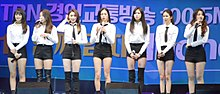 The members of CLC, in white shirts and black shorts, stand on a stage