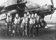 Six young men wearing flying suits standing in front of a World War II-era twin engined monoplane