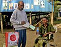 A community TB treatment supporter supervises a TB patient in Western Province PNG taking her daily medication - Photo AusAID (10661548824).jpg