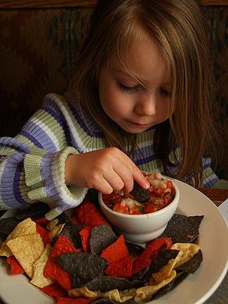 Tortilla chip - A young girl eating tortilla chips with pico de gallo