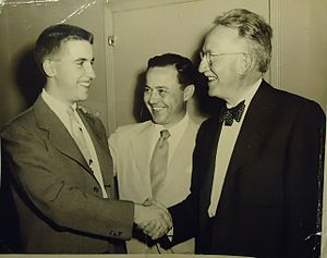 DDB Worldwide - Copywriter Sandy Sulcer (left) shakes hand of Maurice Needham, with Sy Mullen, in 1950.