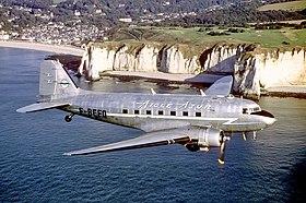 Un DC-3 aux couleurs d'Aigle Azur en Normandie, la falaise d'Aval en arrière-plan.