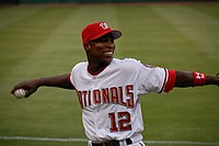 With baseball in hand, an African-American man wearing a white and red Nationals baseball uniform cocks his arm backward as he prepares to throw