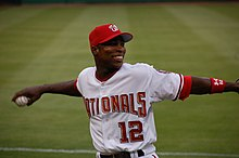 With baseball in hand, an African-American man wearing a white and red Nationals baseball uniform cocks his arm backward as he prepares to throw.