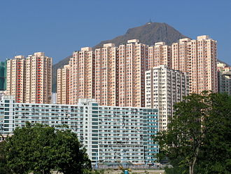 Amoy Gardens - Amoy Gardens blocks standing behind a block of the green coloured (and now demolished) Lower Ngau Tau Kok (II) Estate in 2007. Kowloon Peak is visible in the background.