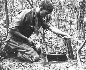 A soldier is kneeling over an open trapdoor on the jungle floor while holding a torch.