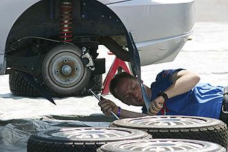 Auto mechanic - A mechanic working on a Ford Focus rally car.