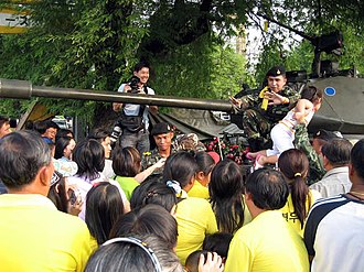 2006 Thai coup d'état - Soldier asking the crowd to move back as people wait to have picture of their children taken with him.
