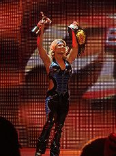 A blond woman, wearing a black and blue catsuit with the sides of the torso removed to bare part of her midriff, standing with both arms in the air while holding a gold statuette in her right hand and a wrestling championship in her left.