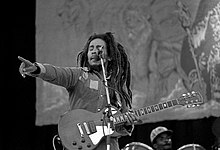 Black and white image of Bob Marley on stage with a guitar