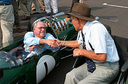 Two elderly men shake hands on a race starting grid. One is sitting in a green racing car, the other in a wheelchair.