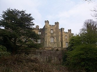 Brancepeth Castle - West side of the castle. The 19th-century addition to an older section of the castle can be seen below the left turret. In the foreground is Japanese knotweed.