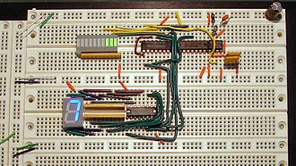 Dual in-line package - An operating prototyped circuit on a solderless breadboard incorporating four DIP ICs, a DIP LED bargraph display (upper left), and a DIP 7-segment LED display (lower left).
